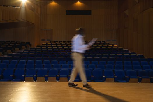 Businessman practicing and learning script while walking in the auditorium