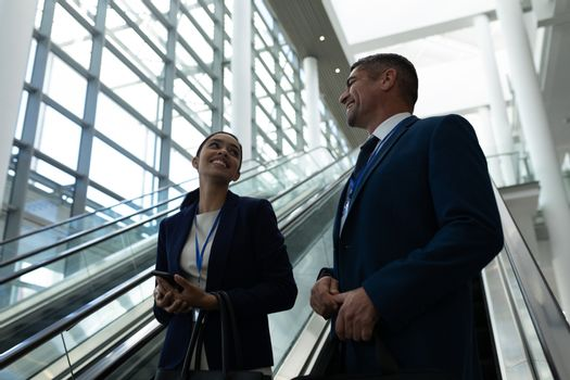 Mixed-race of businessman and businesswoman interacting with each other near escalator