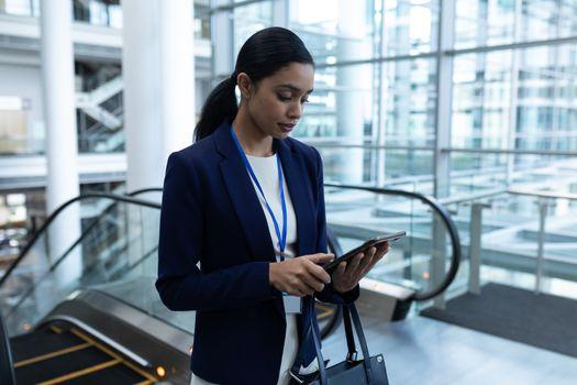 Mixed-race businesswoman using digital tablet near escalator