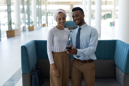 Young mixed-race couple using mobile phone in the lobby
