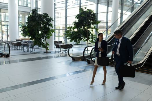 Caucasian businessman and mixed-race businesswoman interacting with each other while moving down on