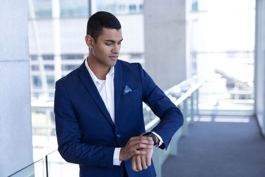 Young mixed-race businessman using smartwatch in modern office