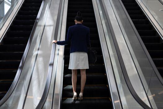 Beautiful mixed-race businesswoman using escalator