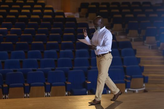 Businessman with holding script walking in a auditorium