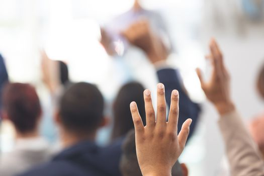 Hands raised in a business seminar