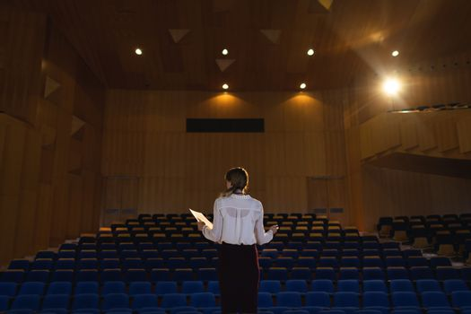 Businessawoman practicing and learning script while standing in the auditorium