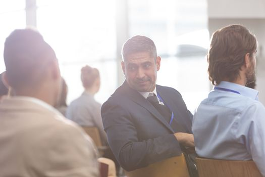 Businessman interacting with his colleague during seminar