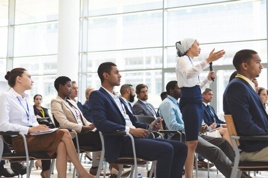 Businesswoman asking question during seminar