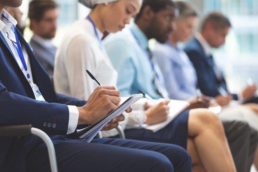 Businessman writing on notepad during seminar