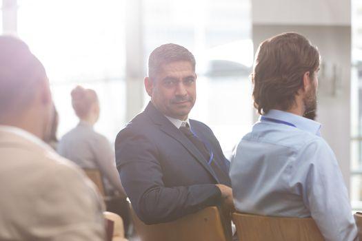 Businessman looking at camera during seminar