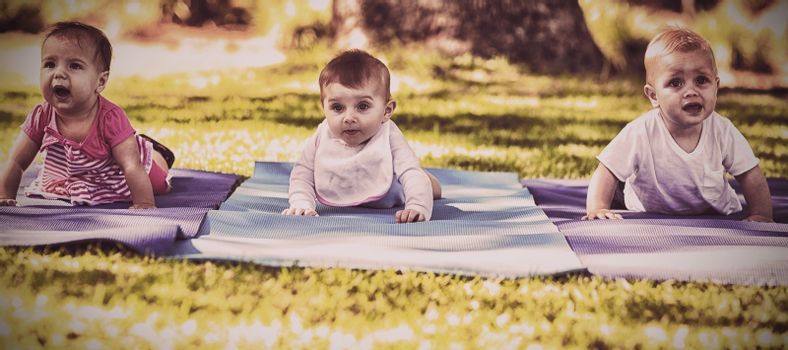 Three babies crawling on exercise-mat in park