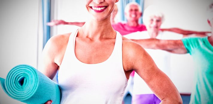 Portrait of Instructor holding yoga mat during sports class