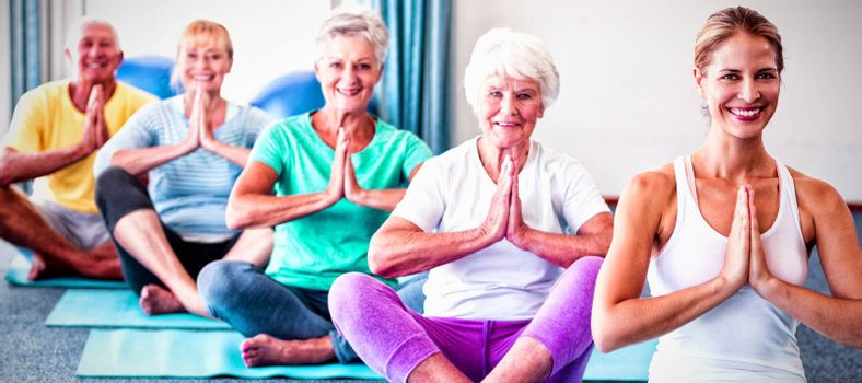 Instructor performing yoga with seniors during yoga class