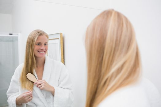 Happy blonde brushing her hair