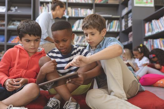 Schoolboys using a digital tablet while they are sitting on cushions in a library