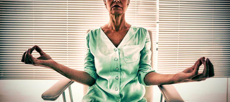 Senior woman doing yoga on chair at fitness studio