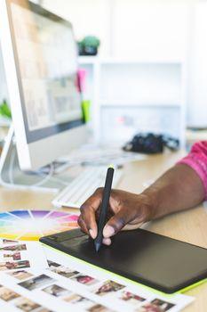 Graphic designer working on graphic tablet at desk