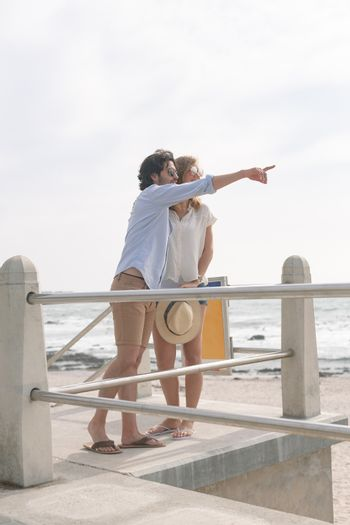 Caucasian couple interacting with each other on the promenade at the seaside