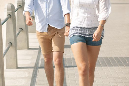 Caucasian couple walking on the promenade at the seaside