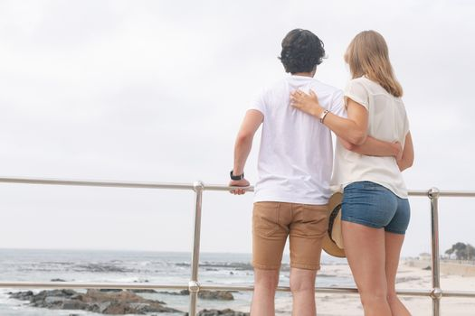 Caucasian couple standing on the promenade at the seaside