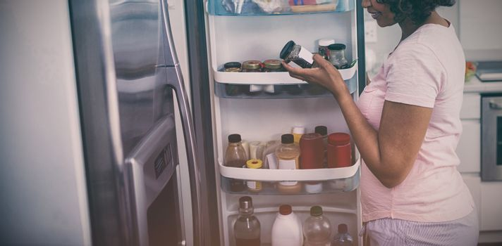 Woman removing bottle from refrigerator in kitchen