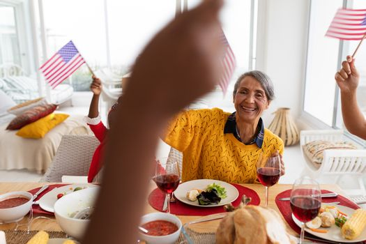 Side view of Multi-generation African American family holding American flag and having celebration on a dining table at home