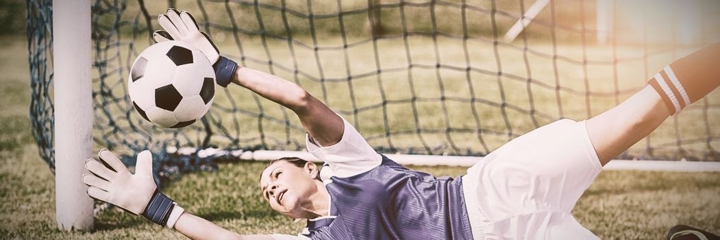 Female goalkeeper saving a goal