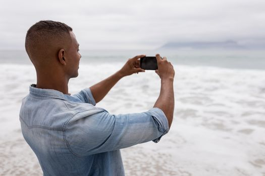 Man clicking pictures of sea with mobile phone