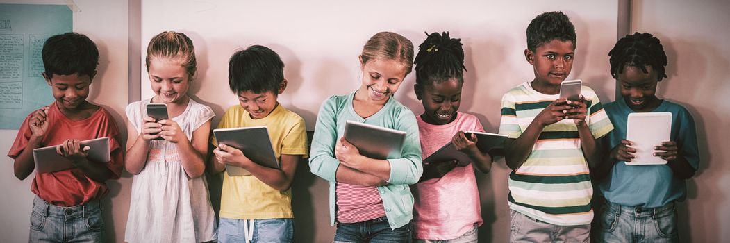Happy pupils standing with technology against wall in classroom