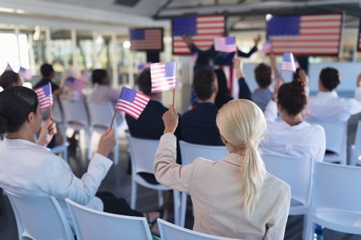 Business people waving an American flag in business seminar