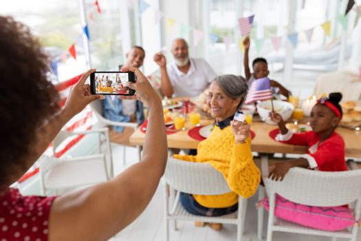 Woman clicking photo of her family with mobile phone