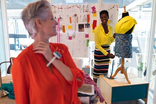 Front view of diverse female fashion designers interacting with each other in design studio. This is a casual creative start-up business office for a diverse team