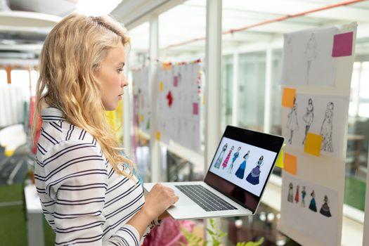 Female graphic designer using laptop in design studio