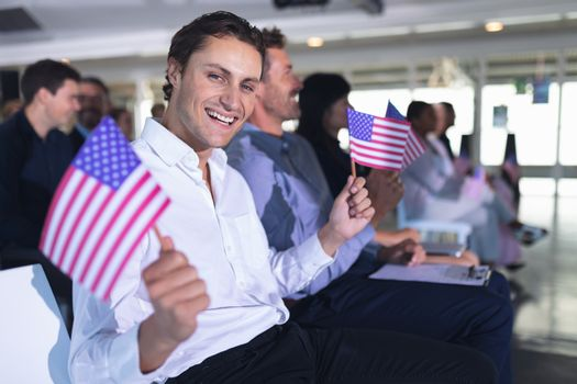 Businessman waving an American flag in business seminar