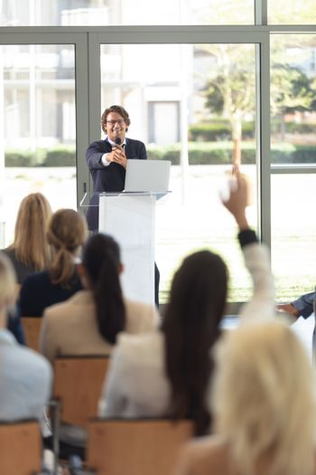 Mature Caucasian male executive doing speech in conference room, answering question