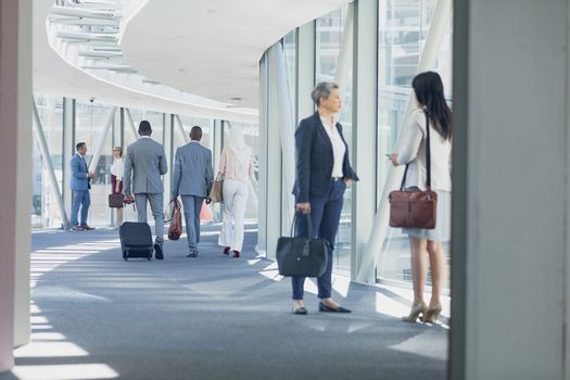 Businesswomen interacting with each other in corridor