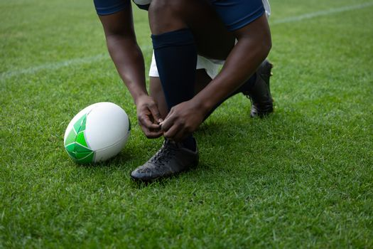 African american male rugby player tying shoelaces in the stadium
