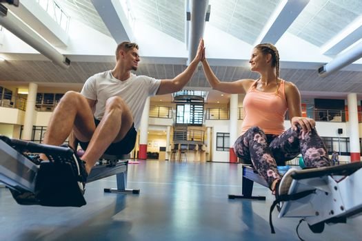 Low angle view of young fit Caucasian male and female athlete giving high five in fitness center. Bright modern gym with fit healthy people working out and training