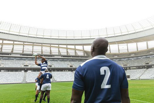 Group of diverse male rugby player playing rugby match in stadium