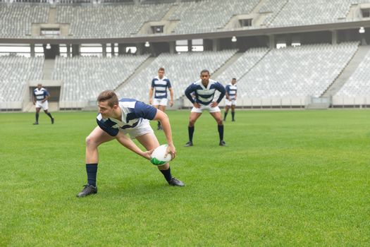 Group of diverse male rugby players playing rugby match in stadium