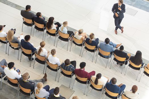 Diverse executives sat in conference room, looking speech