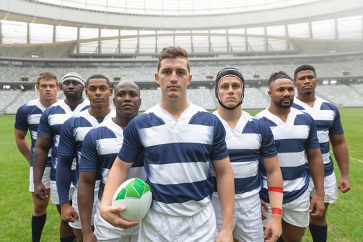 Group of diverse male rugby players standing together with rugby ball in stadium