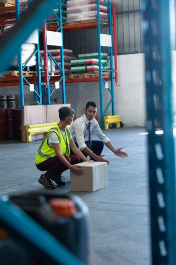 Male staff giving training to female staff in warehouse