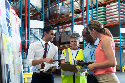 Warehouse staffs discussing over clipboard in warehouse