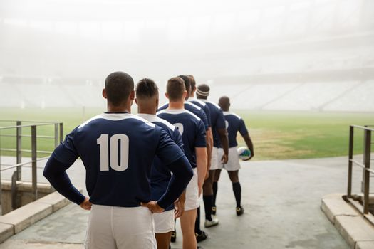 Diverse male rugby players standing at the entrance of stadium in a row for match