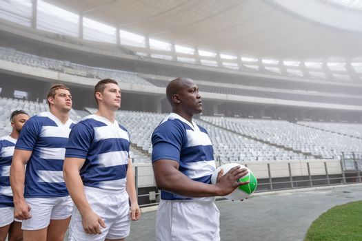 Diverse male rugby player standing in a row at the entrance of stadium