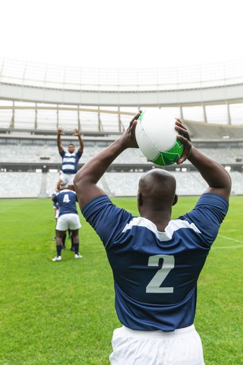 African American male rugby player throwing rugby ball in stadium