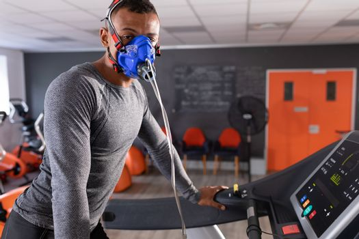 Side view of an African-American athletic man doing a fitness test using a mask while using a treadmill inside a room at a sports center. Bright modern gym with fit healthy people working out and training. Athlete testing themselves with cardiovascular fitness test on exercise bike