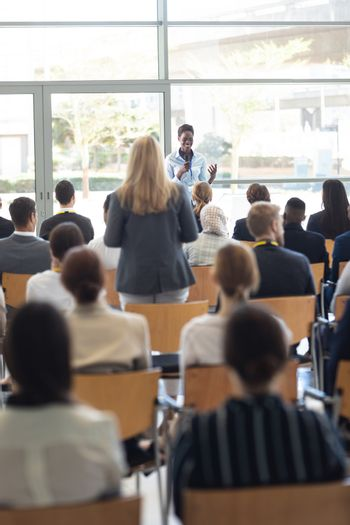 Front view of young African american businesswoman doing speech and answering questions in conference room