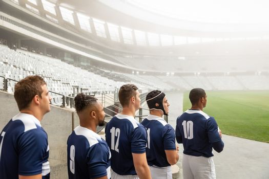 Group of diverse male rugby players standing at the entrance of stadium in a row for match